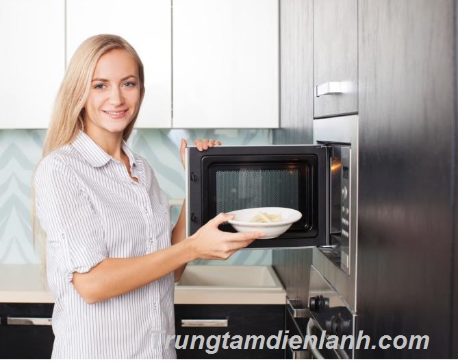 Woman warms up food in the microwave